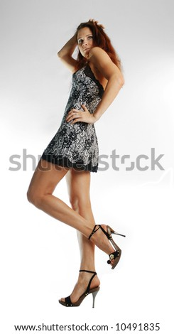 Sunburnt model in lacy short dress and slim legs in black sandals - stock photo