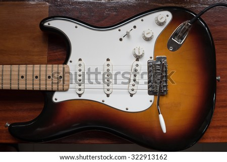 Sunburst color guitar with wooden table in background - stock photo