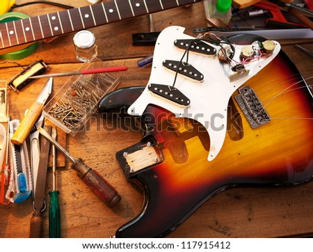 Sunburst electric guitar on guitar repair desk or in a repair work shop. Neck and pickguard detached. Double cutaway solid body guitar. Shallow depth of field. - stock photo