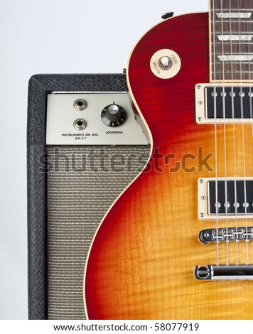 Sunburst electric guitar standing up against a vintage amp with inputs and knob showing - stock photo
