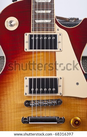 Sunburst electric guitar with old amplifier in the background - stock photo