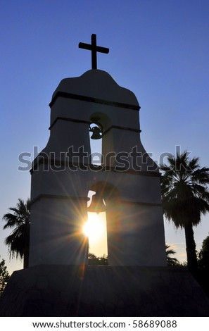 Sunburst through silhouetted mission bell tower. - stock photo