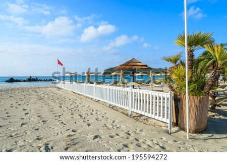 Sunchairs and white wooden fence on Porto Giunco beach on sunny day, Villasimius, Sardinia island, Italy