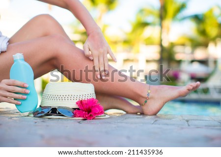 Suncream, hat, sunglasses, flower and tanned female legs near pool - stock photo