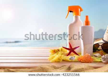 Suncream on towel and wooden slats with shells. Sun shine and sea background. Horizontal composition. Front view - stock photo