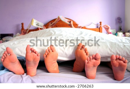 Sunday morning, a family  reading in bed - stock photo