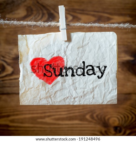 Sunday on red heart on aged paper hanging on the clothesline. On old wood background - stock photo