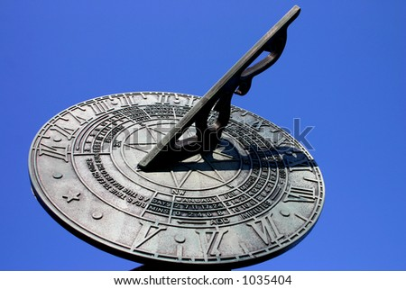 Sundial against pure blue summer sky - stock photo