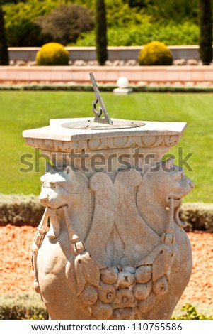 Sundial on green garden - stock photo