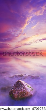 Sundown on sea with bright color on the sky and stone on foregrounds. Vertical panorama - stock photo
