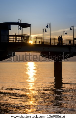 Sundown over Miedzyzdroje pier, Poland, Baltic sea - stock photo