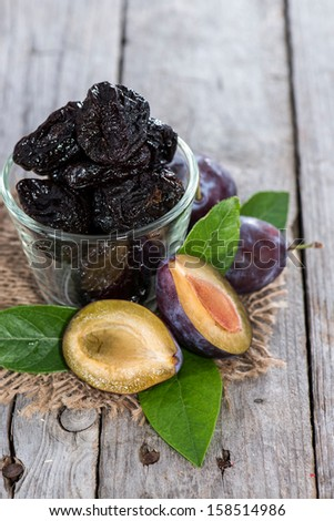 Sundried Plums on vintage wooden background - stock photo