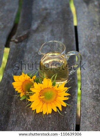 sunflower and sunflower oil on wooden table - stock photo