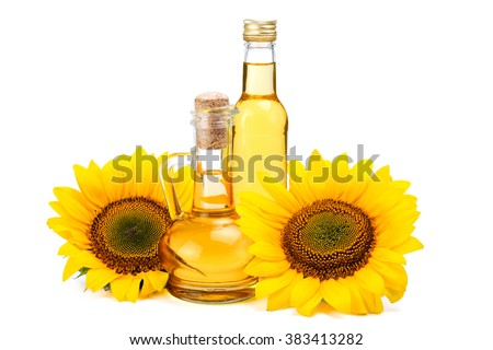 Sunflower oil in vintage glass bottles with two fresh sunflowers isolated on white background - stock photo