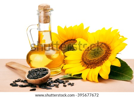 Sunflower oil, spoon with seeds and flowers lays on wooden table  - stock photo