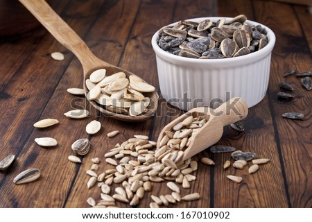 sunflower seeds and pumpkin seeds on wood background - stock photo