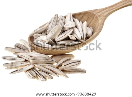 Sunflower seeds on wooden spoon isolated on white background - stock photo