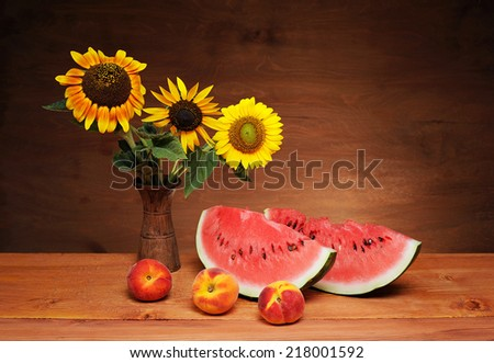 Sunflowers in a vase and watermelon on the table - stock photo