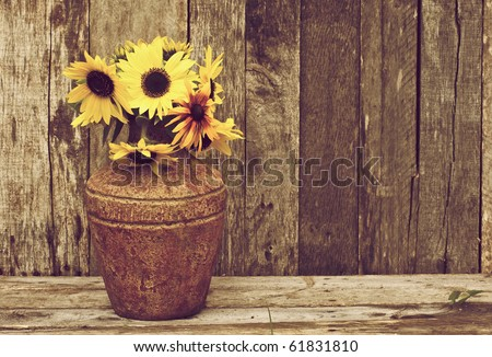 Sunflowers in a vase on a rustic, grunge background with copy space. - stock photo