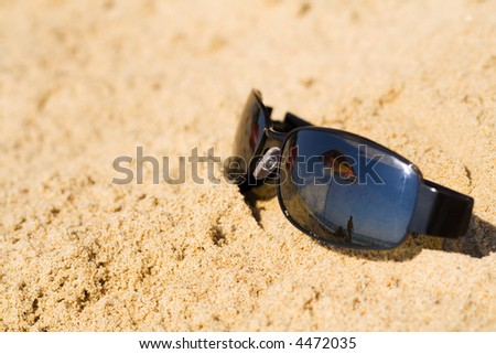 Sunglass in the sand reflecting beach umbrella and summer sky - lots of copy space - stock photo