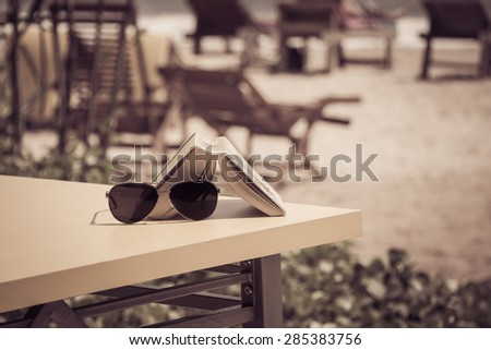 Sunglasses and book lying on a table in a tropical beach cafe. Vacation theme concept. Retro style effect - stock photo