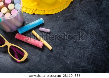 Sunglasses and chalk on black chalkboard from above. Summer vacation concept. Background with copyspace - stock photo