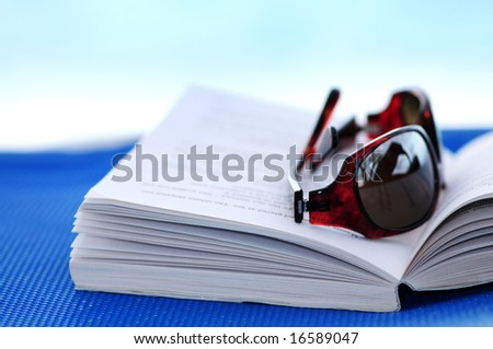 Sunglasses and open book on beach chair - summer vacation concept - stock photo