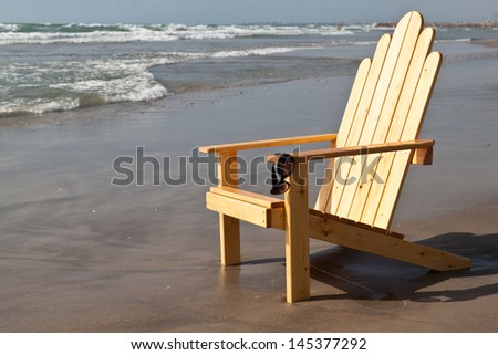 Sunglasses and sun lounger by the sea in summer