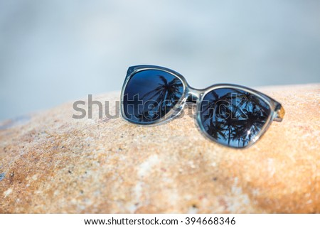 Sunglasses closeup in tropical country - palm trees reflection on lenses - stock photo