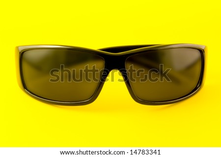 Sunglasses isolated on the yellow background - stock photo