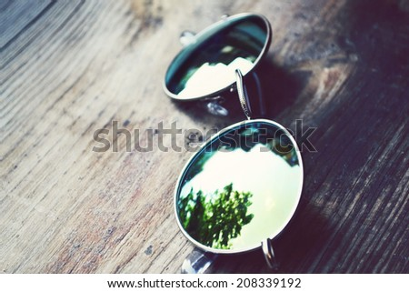 Sunglasses lying on wooden table with a reflection of trees - stock photo