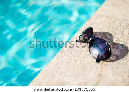 Sunglasses near swimming pool - stock photo