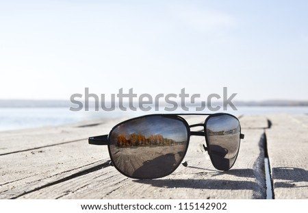 Sunglasses on wooden table - stock photo