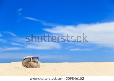 Sunglasses over coconut fruit on sandy beach under hot shiny sun light looked like a happy (tourist) man lying on the beach during holiday summer vacation on wonderful trip under bright blue sky. - stock photo