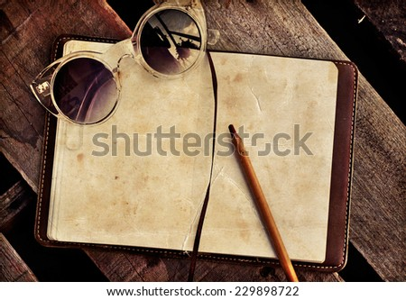 Sunglusses, White blank papers in a copybook with a pen on the wooden desk