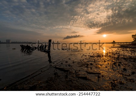 Sunken boat with distant jetty on a glory morning - stock photo