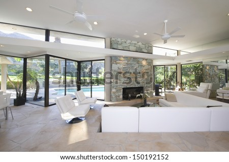 Sunken seating area and exposed stone fireplace in spacious living room with view of swimming pool at home - stock photo