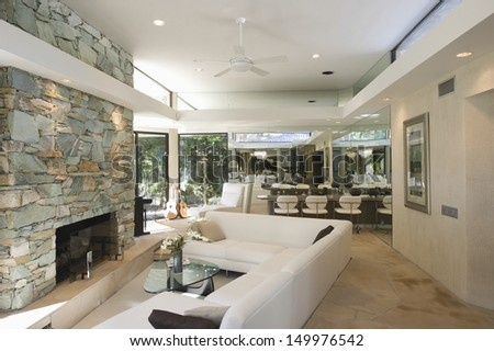 Sunken seating area and stone fireplace with dining area in background at home - stock photo