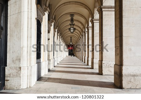 Sunlight and shadows in long marble covered corridor with ornate wrought iron lamps hanging from vaulted ceiling in the buildings surrounding the Praca Del Comercio Lisbon Portugal
