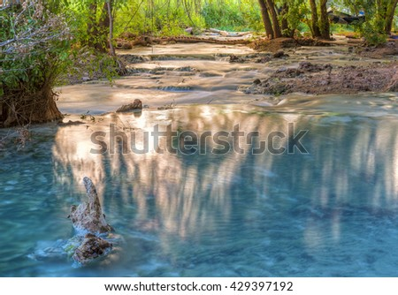 Sunlight bounces off the far cliffs and lights up reflections in Havasu Creek on the Havasupai Indian Reservation in the Grand Canyon. - stock photo