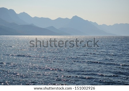 Sunlight emerging behind Biokovo mountain during early morning. Croatia - stock photo