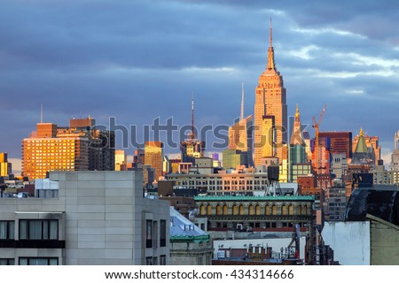 Sunlight glows on the buildings of New York City at sunset in Manhattan - stock photo