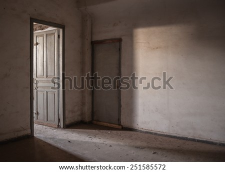 Sunlight is falling through an empty room of an old, deserted building. - stock photo