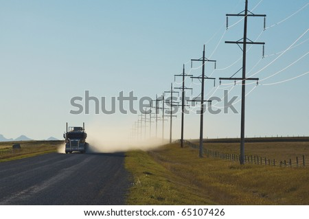 Sunlight on electrical power lines with truck on gravel road - stock photo