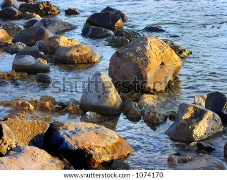 Sunlight on Rocks and Water - stock photo