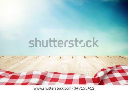 Sunlight on summer sky with wooden picnic table in red tablecloth - stock photo