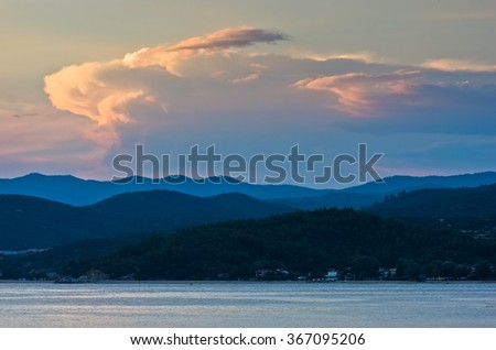 Sunlight reflected on clouds after sunset at Toroni bay with mountains in background, west coast of Sithonia, Greece - stock photo