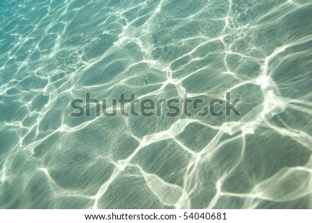 Sunlight reflecting on a the bottom of a shallow underwater bay. - stock photo