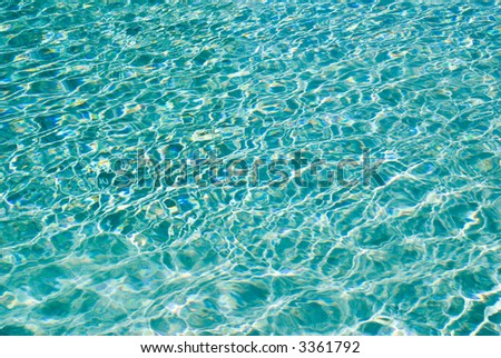 Sunlight ripples on turquoise water in a holiday resort swimming pool - stock photo
