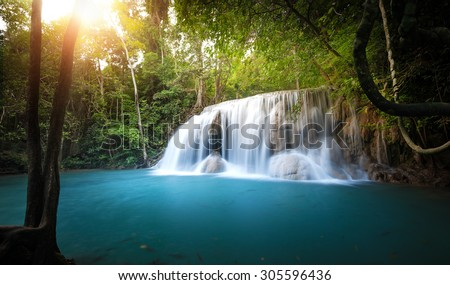 Sunlight shines through trees and leaves of tropical forest and waterfall flows into blue water pond - stock photo